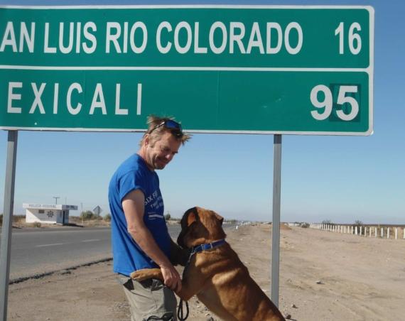 A picture of a man and a dog in the side of a Mexican Direction Signage