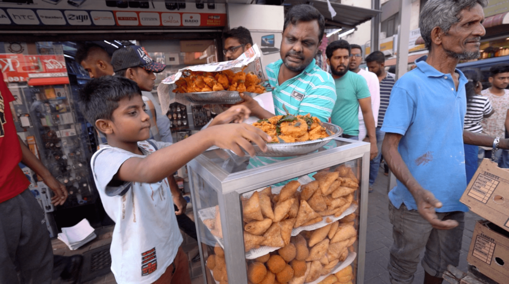 Street Food being sold at a public market in Colombo, Sri Lanka surrounded by an audience