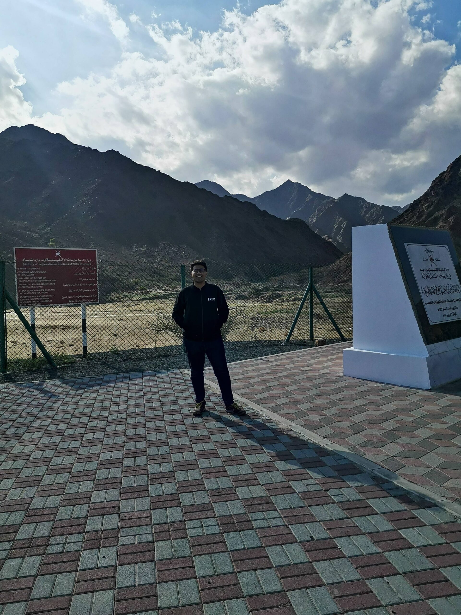 Tarun standing near Al Sadah Dam board with Mountains behind him