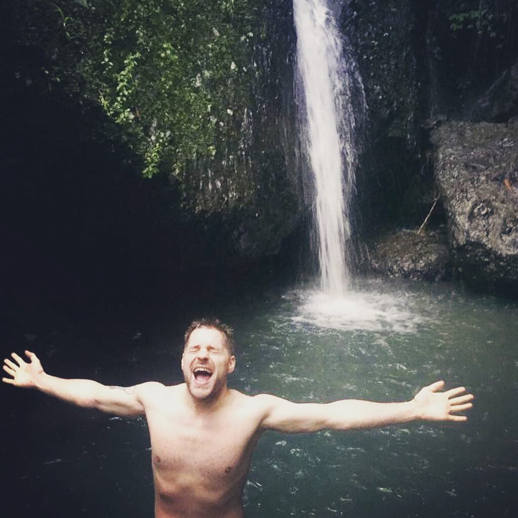 Eivind from Norway Couch surfing is posing celebratory near a waterfall in Java, Indonesia
