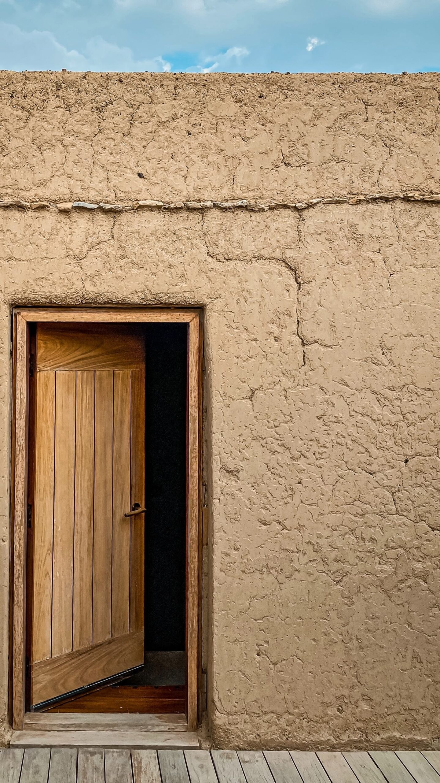 A door in a an old housing with wall having slight fringes forming